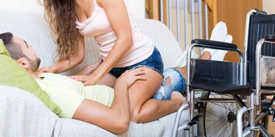 Девушка и парень инвалид на кровати. возле стоит инвалидное кресло