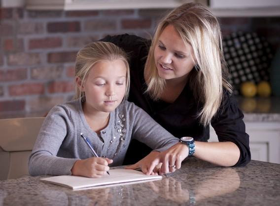 Домашнее образование. Мама и дочь сидят за столом за тетрадью
