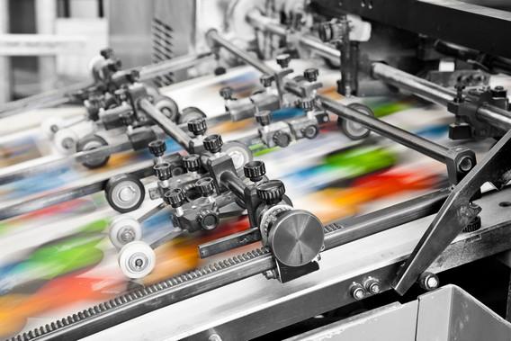 Цветная офсетная печатная машина за работой в типографии. Крупный план