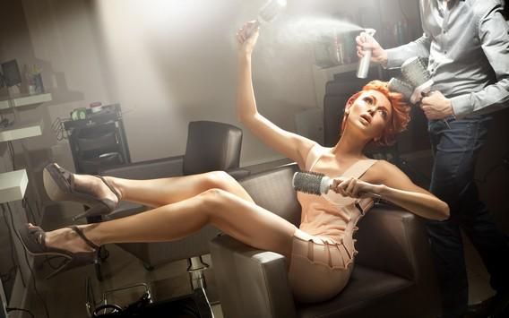 Рыжая девушка в мини юбке в кресле парикмахера с расческами в руках