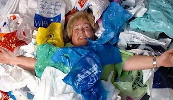 женщина лежит на множестве полиэтиленовых пакетов разного цвета