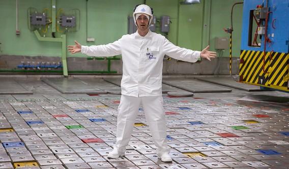 Работник реакторного цеха АЭС стоит на топливных стержнях из графита в атомном реакторе