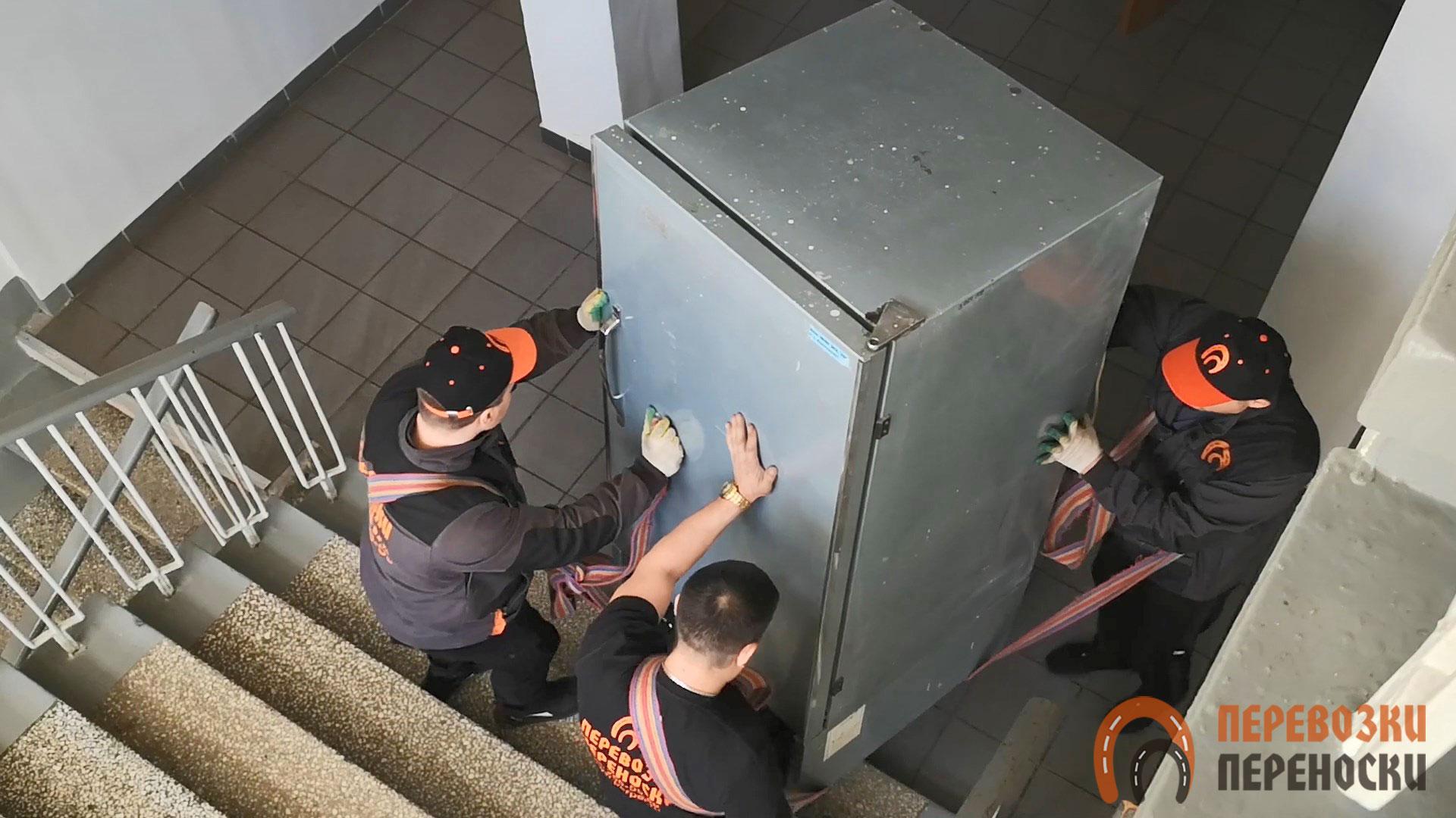 Такелаж промышленного холодильника по лестнице тремя грузчиками