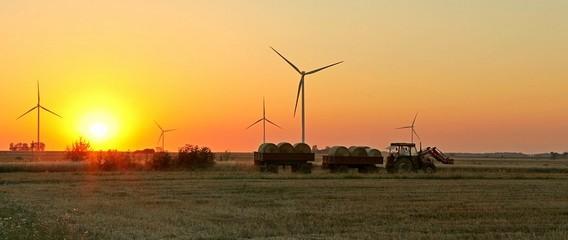 Ветрогенераторы в поле на фоне заходящего солнца и едущего трактора с тюками сена