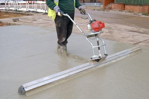 Рабочий идет по бетону с поверхностным вибратором