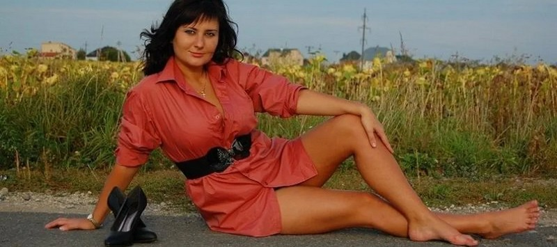 Женщина в красном лежит на асфальте без туфель
