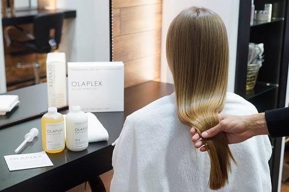 olaplex средство для волос. Блондинка с длинными волосами сидит спиной в парикмахерской